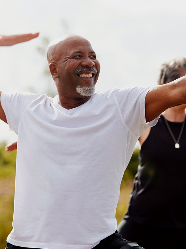 Older man participating in outside yoga.