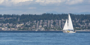 Lake in Edmonds, WA with residential buildings in the background and a white sailboat in the water.