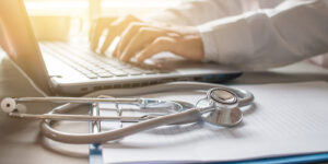 Doctor typing on laptop with documents and stethoscope on the side.